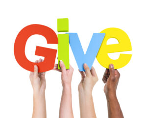 """Hands holding up letters that spell """"GIVE"""""""